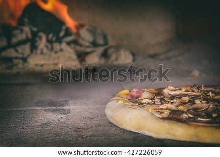 Fresh original Italian pizza in a traditional wood-fired stone oven. - stock photo