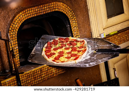 Fresh original Italian pizza on a shovel is putting into a traditional wood-fired stone oven. - stock photo