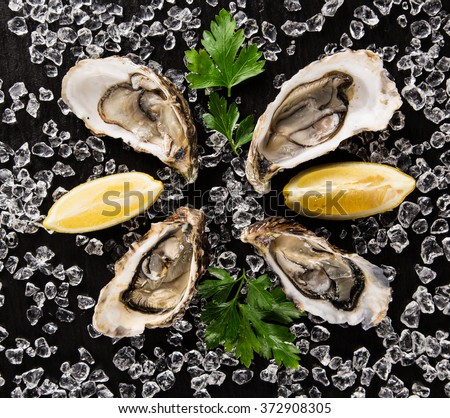 Fresh oysters on a black stone plate top view - stock photo