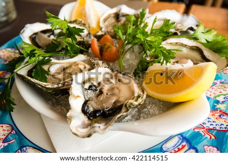Fresh oysters on a white plate with ice and lemon on a colorful restaurant napkin - stock photo