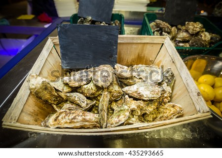 Fresh oysters on the shelf for sale at the fish market. Wide angle. - stock photo