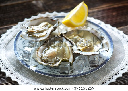 Fresh oysters  with ice and lemon on a wooden background - stock photo