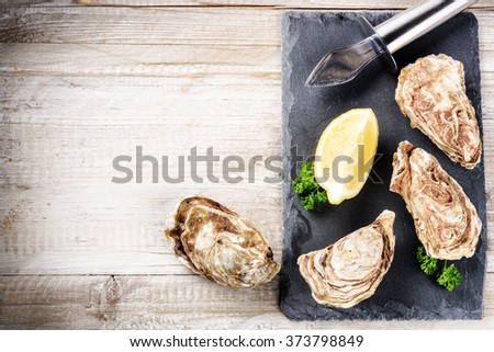 Fresh oysters with lemon on stone plate. Food background  - stock photo