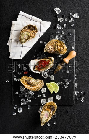 Fresh oysters with tomato salsa on a black stone plate top view - stock photo
