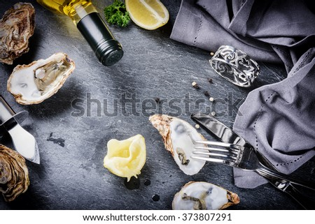 Fresh oysters with white wine and lemon on stone background. Dinner concept  - stock photo