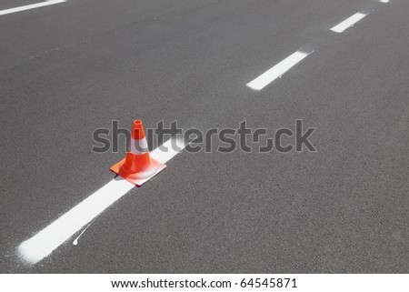 Fresh painted line at asphalt road and traffic cone - stock photo