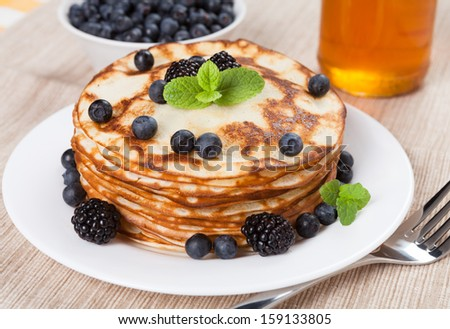 Fresh pancakes with berries and honey  - stock photo