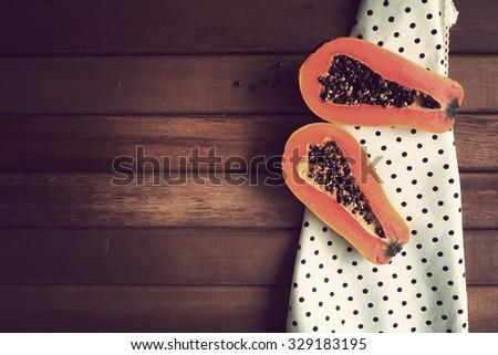 Fresh papaya on wooden background. Vintage effect. - stock photo