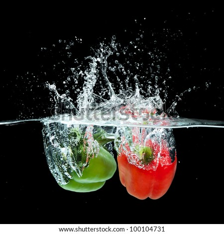 Fresh  paprika splash in water on black background - stock photo