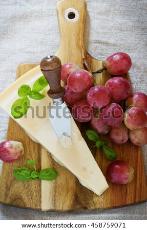 Fresh parmesan cheese and ripe grapes on a table. Health and diet food. Selective focus.Top view  - stock photo