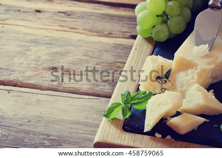 Fresh parmesan cheese and ripe grapes on a table. Tinted image. Health and diet food. Selective focus. Copy space for you text - stock photo