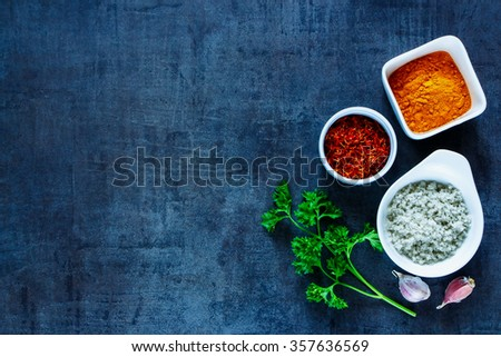 Fresh parsley, garlic and spices in bowls over dark grunge background with space for text. Food and cuisine ingredients. Top view. - stock photo