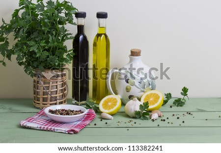 Fresh parsley, garlic, balsamic vinegar, olive oil, peppercorns and lemon on a table. - stock photo