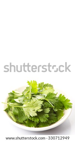 Fresh parsley leaves herb in white bowl over white background