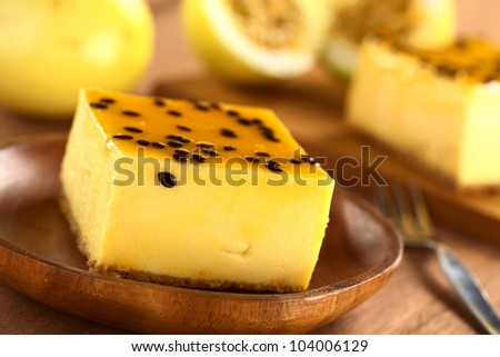 Fresh passion fruit cheesecake dessert on wooden plate with another piece of cake and yellow passion fruit in the back (Selective Focus, Focus on the upper left edge of the cake) - stock photo