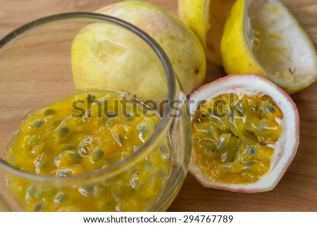 Fresh passion fruit juice with passion fruits on wooden background - stock photo