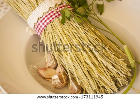 Fresh pasta (tagliolini) uncooked, tied with red and white band and rustic band, on wooden table.