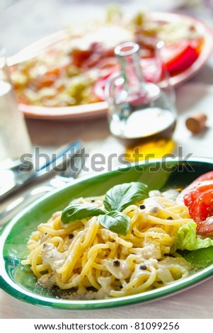 Fresh pasta with pepper sauce and salad - stock photo