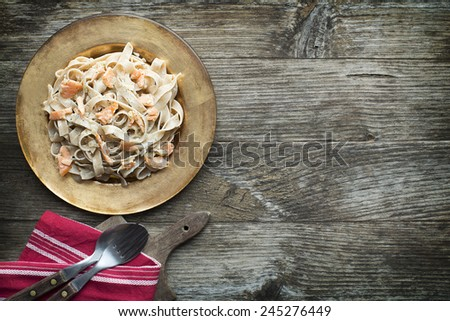 Fresh pasta with smoked salmon in the sauce - stock photo