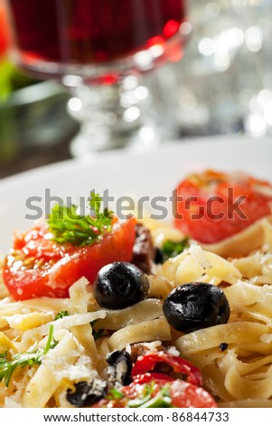 fresh pasta with tomatoes and olives on a plate - stock photo