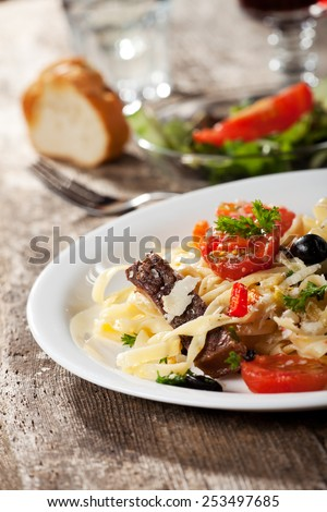 fresh pasta with tomatos and olives on a plate  - stock photo