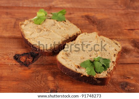 Fresh pate on bread on wooden table - stock photo