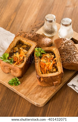 Fresh pea soup in a Bread Bowl, on a wooden board with salt and papper