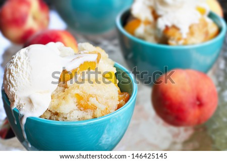 Fresh peach cobbler served with vanilla ice cream. - stock photo