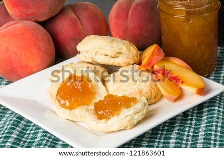 Fresh peach jelly on homemade biscuits with peaches - stock photo