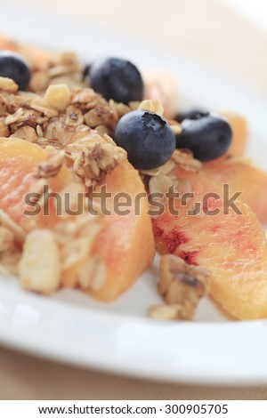 Fresh peaches and blueberries with granola sprinkled over - stock photo