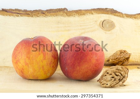 Fresh peaches and peach kernels  on a natural wooden board - stock photo