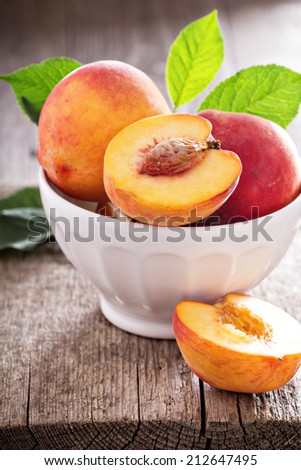 Fresh peaches in a bowl with one cut - stock photo