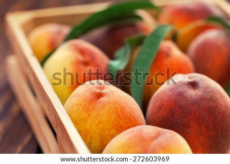 Fresh peaches in a wooden basket - stock photo