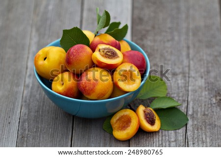 Fresh peaches in blue bowl on wooden table - stock photo