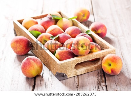 fresh peaches in wooden box - stock photo