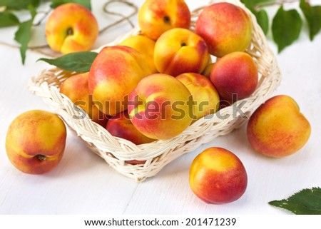 fresh peaches (nectarines) in a basket on a wooden background - stock photo