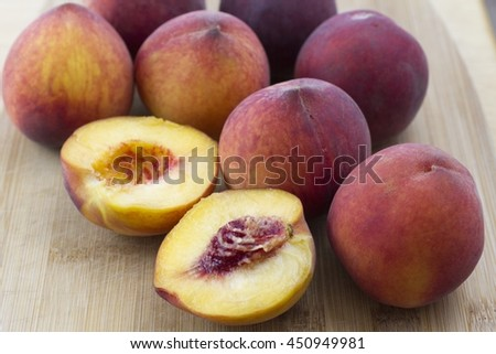 Fresh peaches on a wooden cutting board.