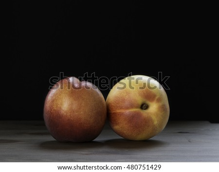 Fresh peaches on wooden black background