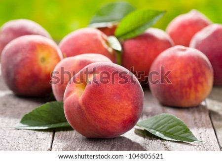 fresh peaches on wooden table - stock photo