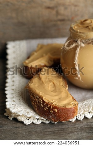 Fresh peanut butter in jar on wooden background - stock photo