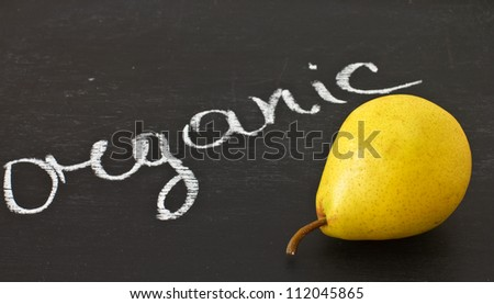 Fresh pear on blackboard and word organic written  by white chalk - stock photo