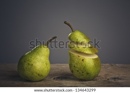 Fresh Pears cut to slices on wooden board - stock photo