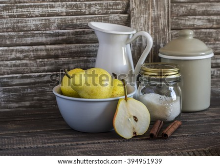 Fresh pears in bowl, cinnamon, sugar and vintage crockery on a dark wooden background. Kitchen still life in rustic style