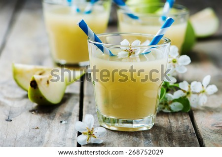 Fresh pears juice on the wooden table, selective focus - stock photo