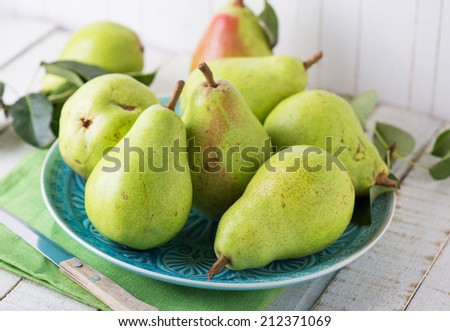 Fresh pears on plate on wooden background.  Selective focus. - stock photo