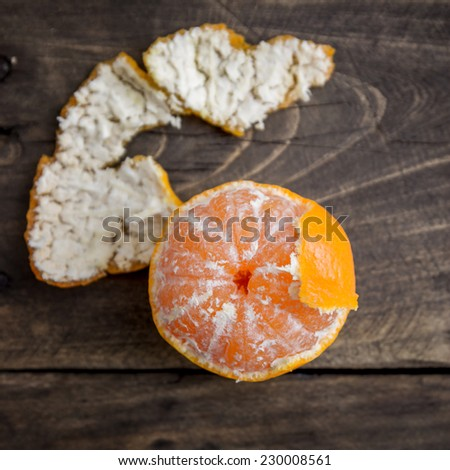Fresh peeled Clementines on wooden board, from above - stock photo