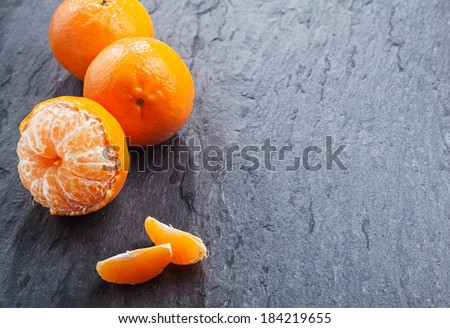 Fresh peeled nectarine for a healthy snack rich in vitamin c with loose segments and two whole fruit arranged as a left-hand border on a slate table with copyspace - stock photo