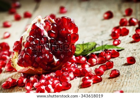 Fresh peeled pomegranates with ruby red beans on old wooden table, selective focus - stock photo