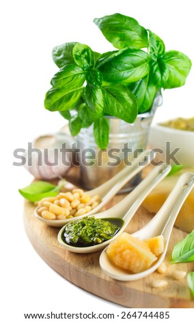 Fresh Pesto and ingredients on a white background,  Shallow depth of field - stock photo
