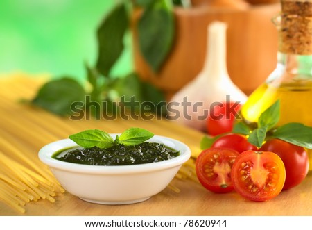Fresh pesto made of basil and cherry tomatoes with olive oil, garlic, mortar, basil and raw spaghetti in the back (Selective Focus, Focus on the basil leaf on the pesto and the tomato in the front) - stock photo